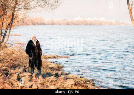 A mature woman wearing a warm fur coat and a woolen cap stays close to the Dnieper river in Kiev, Ukraine, during - Stock Photo