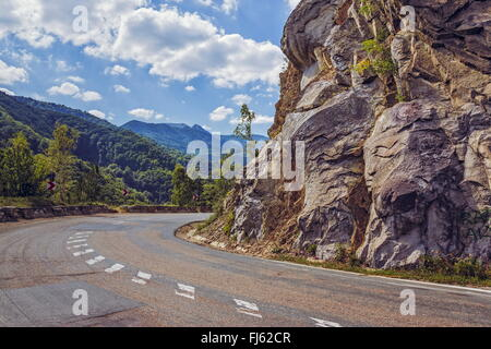 Sunny summer view with steep rocky cliff on the side of a road crossing the Siriu mountains in Buzau county, Romania. - Stock Photo