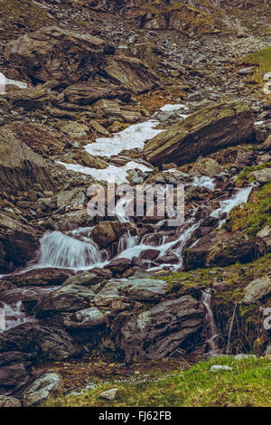 Mountain stream rapids flowing down among rocks nearby the famous Transfagarasan road in Fagaras mountains, Romania. - Stock Photo