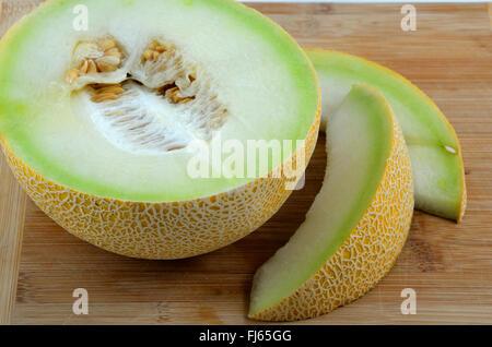 A Galia melon on a wooden chopping board.