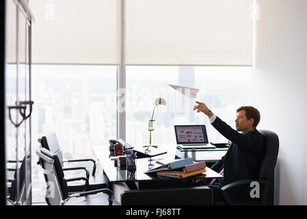 Corporate manager in modern office takes a break and prepares a paper airplane. The bored man dreams of his next - Stock Photo