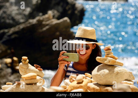 woman taking photos of piles of stones at the bottom of Stairway of the King of Aragon, France, Corsica, Bonifacio - Stock Photo