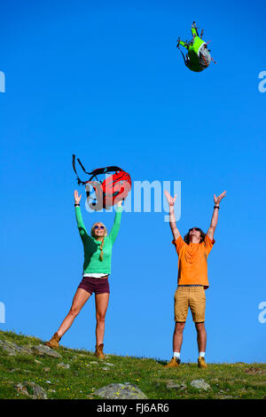 two young people throwing up for joy their rucksacks , France, Savoie - Stock Photo