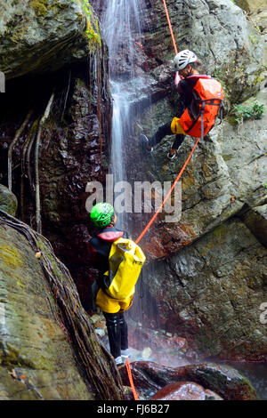two persons rappelling at a waterfall, canyoning , France, Corsica, Bastia - Stock Photo