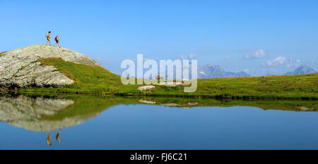 two hikers at mountain lake Lac des Moutons, Mont Pourri in the background, France, Savoie, Vanoise National Park - Stock Photo