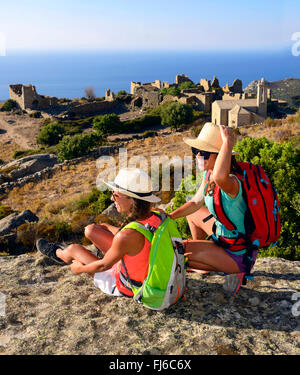 two female hikers taking a break, in the background the abandoned village ruins of Occi, France, Corsica - Stock Photo