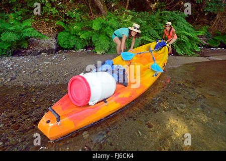 two women pulling their kayak out of the river Golo, France, Corsica, Bastia - Stock Photo