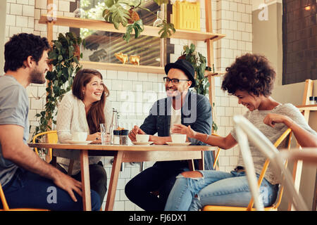 Group of friends enjoying in cafe together. Young people meeting in a cafe. Young men and women sitting at cafe - Stock Photo