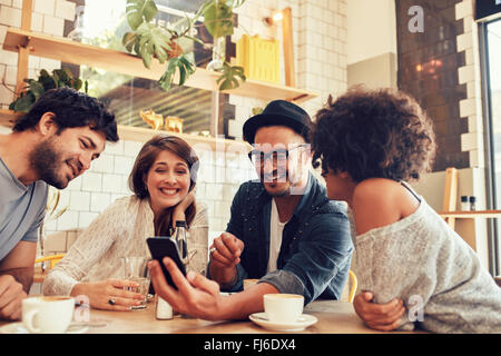 Portrait of a group of young friends meeting in a cafe and looking at the photos on mobile phone. Young men and - Stock Photo