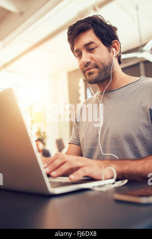 Portrait of young man looking busy working on laptop at a cafe. Caucasian man sitting in coffee shop using laptop. - Stock Photo