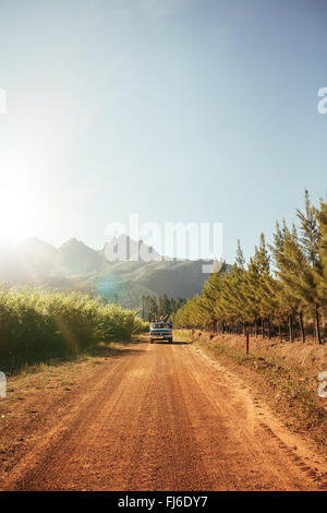 Outdoor image of distant car approaching on a rural dirt road on a sunny day. Automobile driving through the country - Stock Photo