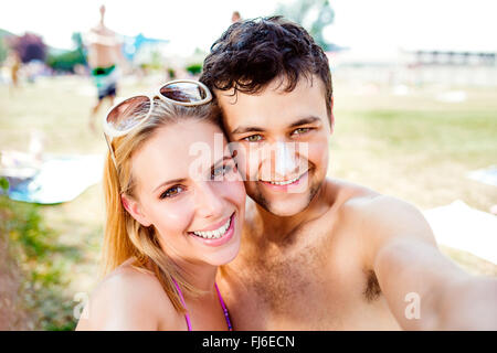 Young couple sunbathing, taking selfie. Sunscreen on the nose. - Stock Photo