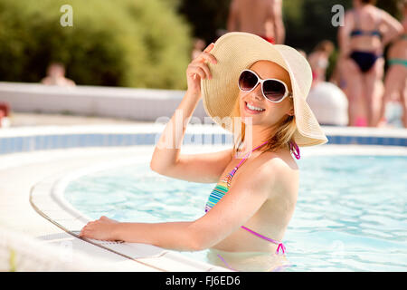 Woman with sunglasses and hat in swimming pool, water - Stock Photo