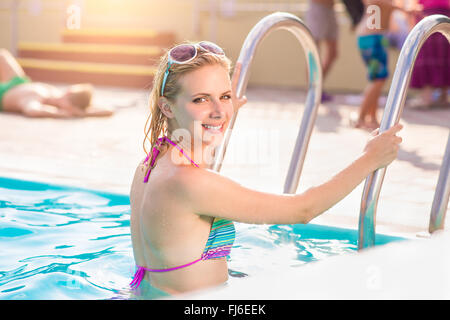 Woman in bikini standing on the pool stairs - Stock Photo