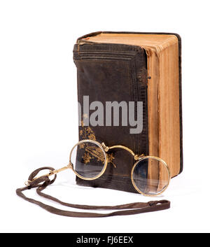 Pair of vintage pince-nez glasses on a thong for reading together with an old worn distressed leather bound book - Stock Photo