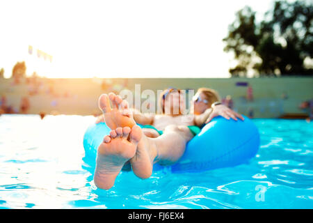 Couple in inflatable ring in pool. Summer and water. - Stock Photo