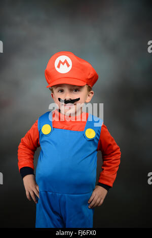Boy dressed up as Super Mario Bros against gray background. - Stock Photo