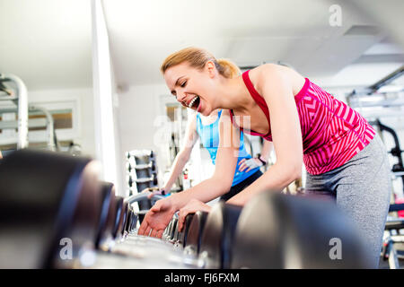 Detail of women in gym laughing, row of weights - Stock Photo