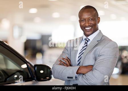 African American car dealership principal standing in vehicle showroom - Stock Photo