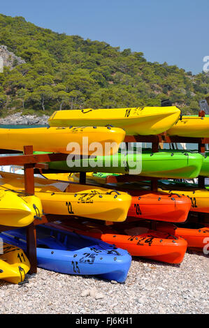 Number of colored plastic rowing boats stacked on the beach - Stock Photo