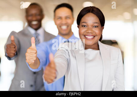 professional vehicle sales team in a row giving thumbs up - Stock Photo