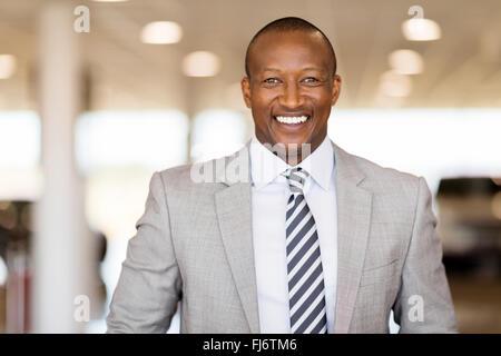 happy African car salesman in showroom - Stock Photo