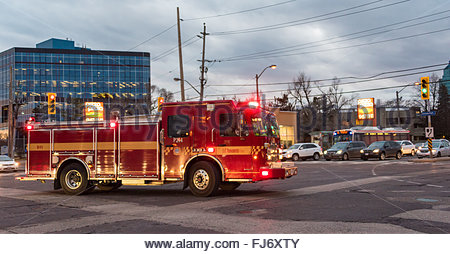 Firetruck from fire department swiftly going to an emergency call, late in the afternoon. - Stock Photo