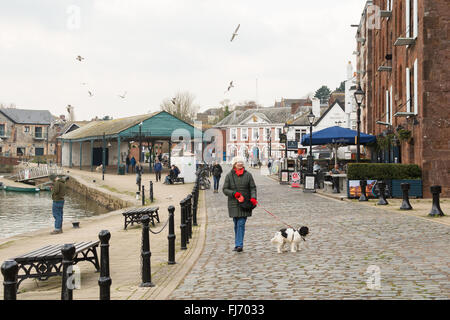 Exeter Quayside - a middle aged woman walking her dog along the side of the River Exe in winter
