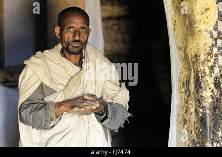 Orthodox priest inside Petros and Paulos rock-hewn church in the Tigray Region, Ethiopia - Stock Photo