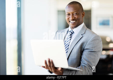 modern afro American vehicle sales consultant using laptop inside showroom - Stock Photo