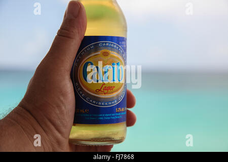 Ice cold Carib beer in mans hand - Stock Photo