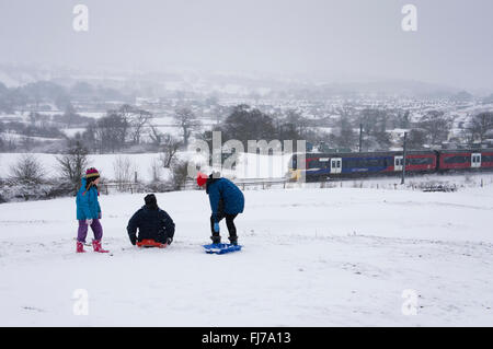 Winter countryside scene - in the snow, a family of 3 with sledges, whilst a train travels past beyond - Burley - Stock Photo