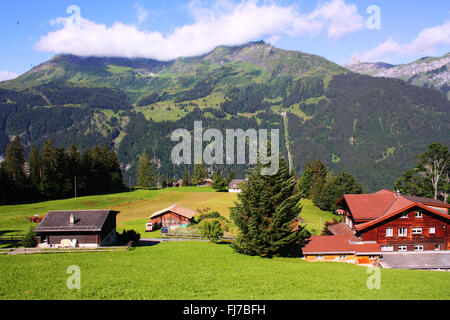 Houses with mountain background in Switzerland - Stock Photo