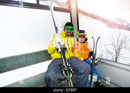 Father and son in ski lift cabin - Stock Photo