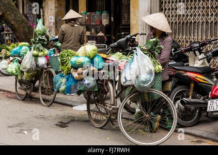 Hanoi, VIetnam - February 2016. Street vendors in Hanoi walking around with their bicycles. - Stock Photo