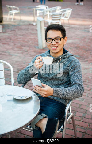 Young asian man sitting and smiling in relaxing outdoor cafe holding cup of coffee and messaging on mobile phone - Stock Photo