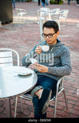Serious young asian man sitting in relaxing outdoor cafe holding cup of coffee and using mobile phone - Stock Photo