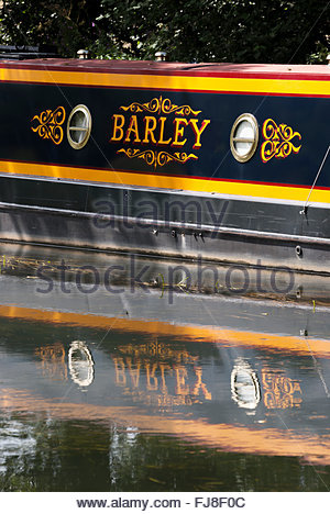 Side of a narrow boat called Barley along with its reflection in the water of the Wey Navigation, Surrey - Stock Photo