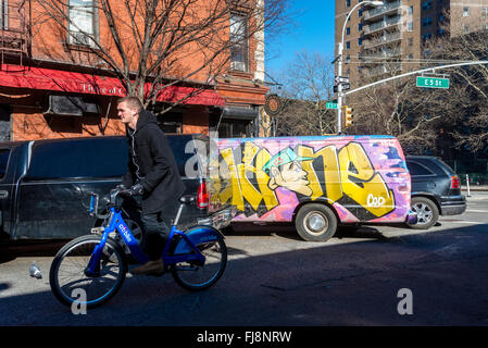 New York, NY 26 Feb 2016 - Man wearing ear pods and riding a CitiBike in the East Village ©Stacy Walsh Rosenstock - Stock Photo