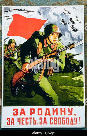 Soviet russian patriotic propaganda poster from World War II with image of soldier going on attack with rifle - Stock Photo
