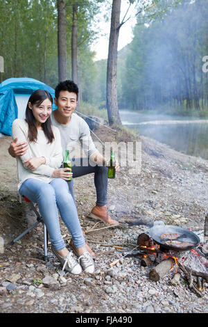 Young Chinese couple sitting beside campfire preparing food - Stock Photo