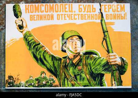 Soviet russian patriotic propaganda poster from World War II with image of soldier going on attack with rifle and - Stock Photo