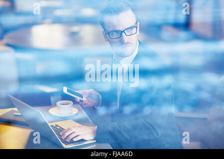 Serious employee with cellphone typing on laptop - Stock Photo