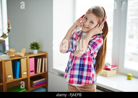 Pretty teenage girl listening to her favorite music at home - Stock Photo