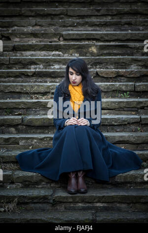 Young woman sat on the stairs outdoors - Stock Photo
