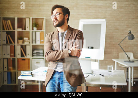 Young businessman standing near his workplace and thinking - Stock Photo