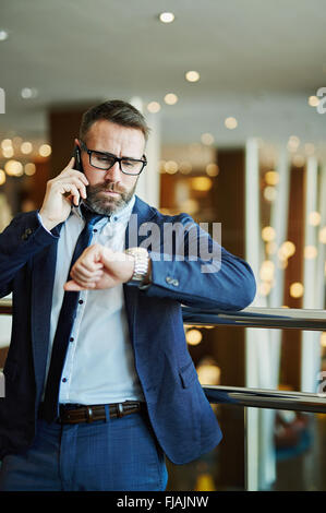 Confident businessman looking at his watch while talking on the phone - Stock Photo