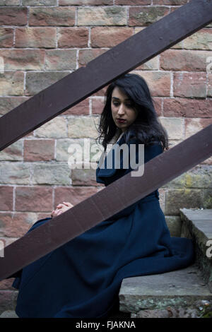 Sad young woman sat on the stairs outdoors - Stock Photo