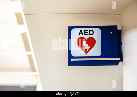 Automated External Defibrillator AED sign mounted to a wall at an airport. - Stock Photo