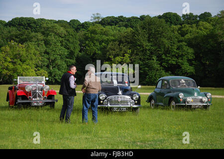 thirties Morris 10/6, fifties Morris Oxford MO and sixties Morris Minor owners chatting at national meeting Cornbury - Stock Photo